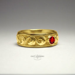 Gold ring or wedding band with baroque scroll work engraved by hand, centered by a bezelled ruby or other select gemstone