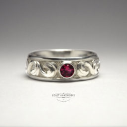 Traditional baroque scroll hand carved in white gold with bezelled ruby on top